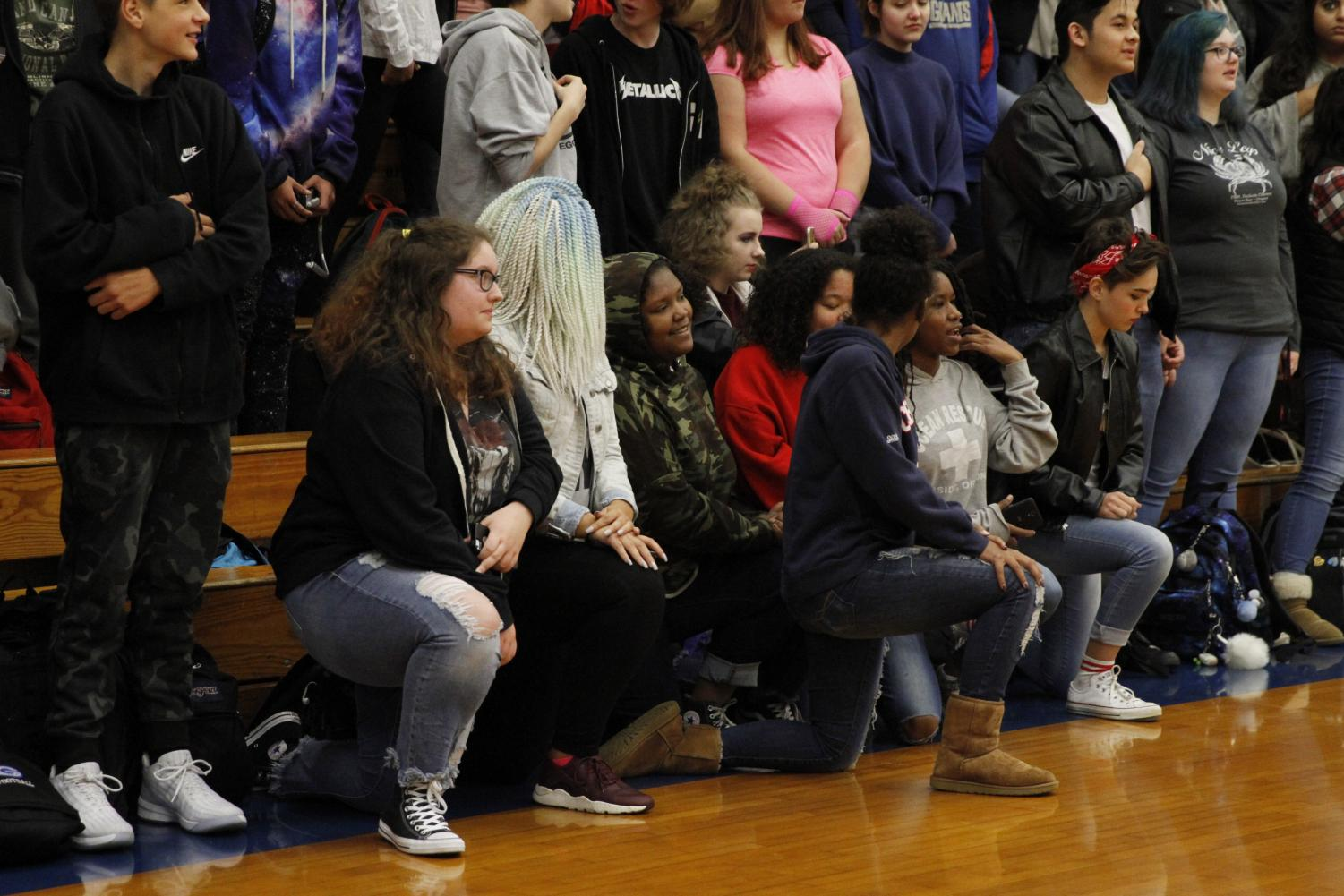 Students take a stand by kneeling during the anthem