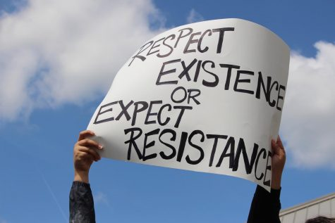 """A poster above the crowd reading """"Respect existence or expect resistance""""."""
