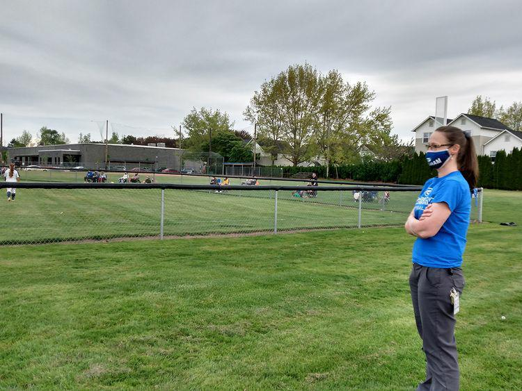 Varsity Softball game being monitored by Ms. Voelker. New COVID-19 guidelines are enforced at Gresham High